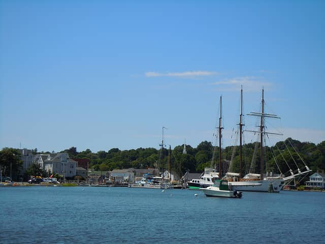 view of boats docked in the water and houses in the background in Mystic, CT