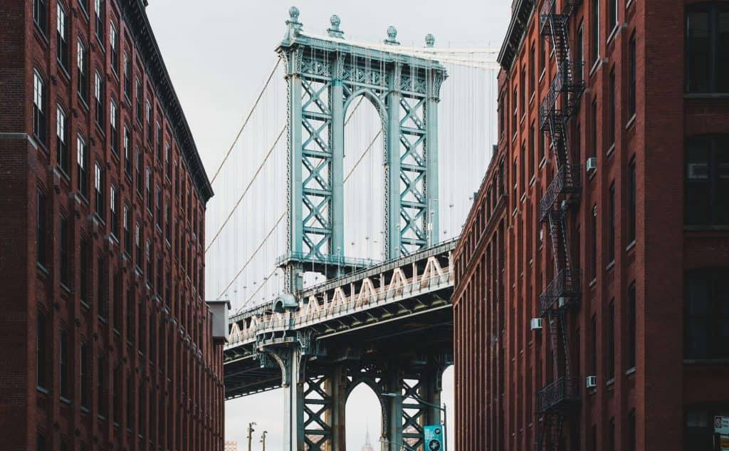 street view of the Brooklyn bridge between two rows of buildings