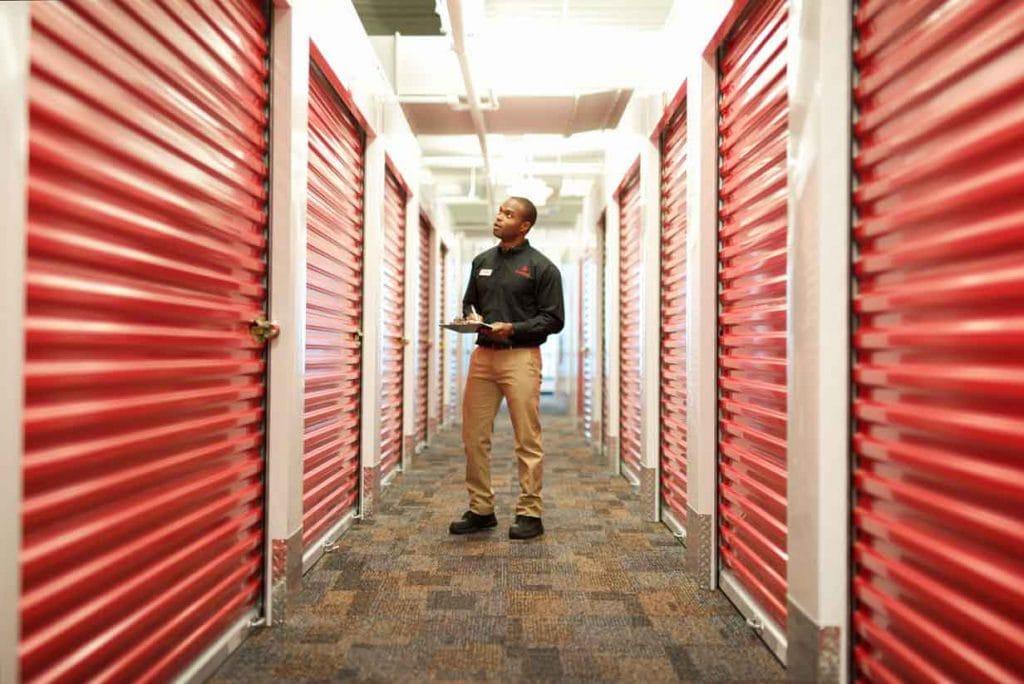 store manager walking through hallway inspecting storage unit doors