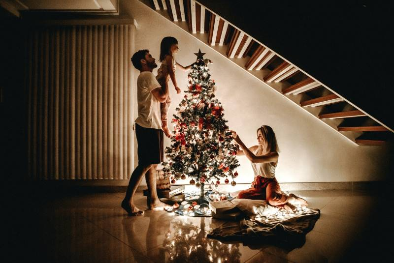 lit holiday tree with young family