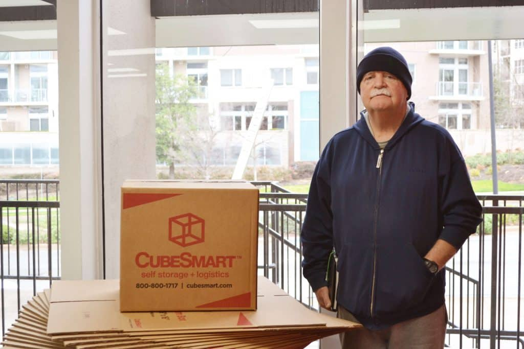 Bob Whilhite standing next to CubeSmart boxes