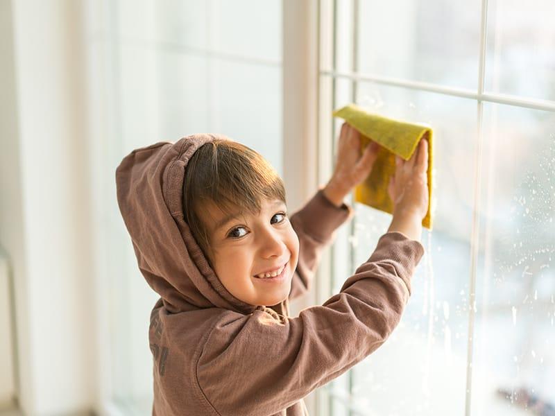 child wiping windows