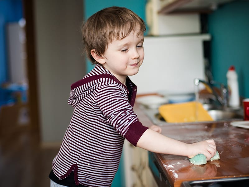 child wiping kitchen counter