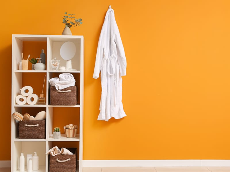 vertical shelving unit and robe hanging on wall hook