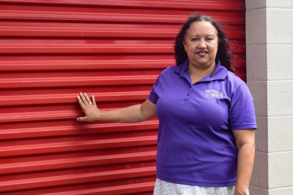 Rev Vanessa Tinsley standing next to her storage unit