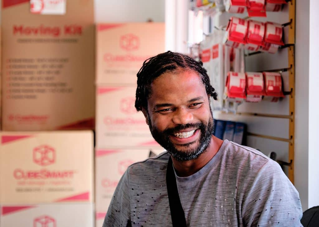 CubeSmart customer Rod Hart smiling in front of moving boxes