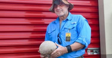 Rudolph Pascucci holding an artifact outside of his storage unit