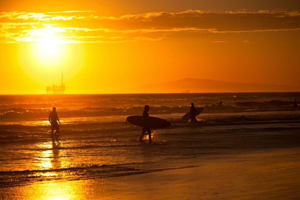 Surfers at sunset near Seal Beach, California