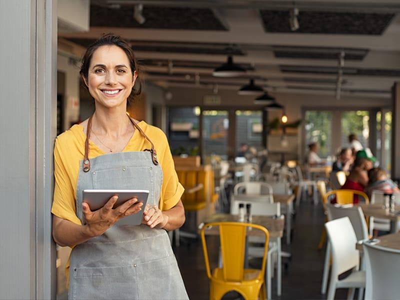 women in yellow shirt holding tablet in restaurant