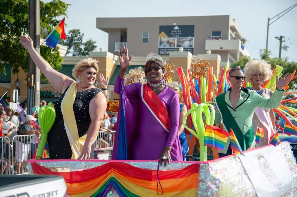 people waving on a float during a parade in Wilton Manors, Florida