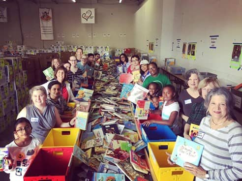 children and adults gathered around a long table with tons of books