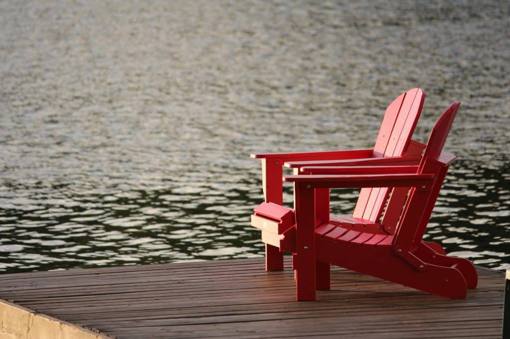 red Adirondack chairs on a pier