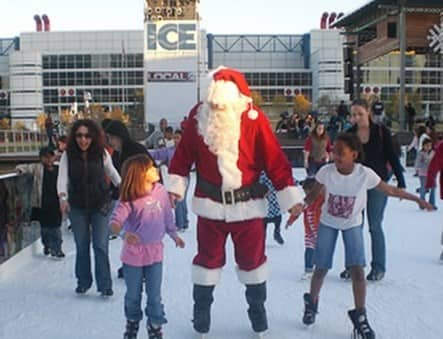 Santa skating outdoors with children
