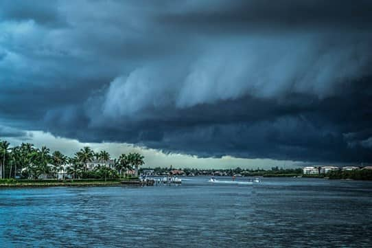 dark storm clouds hovering over the water and the shore