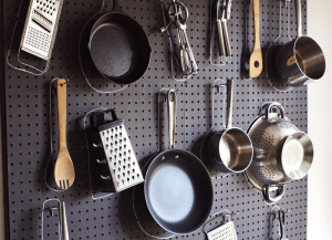 pots and pans hanging on a pegboard