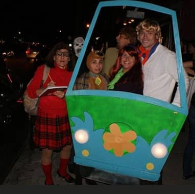 Group of adults dressed in costumes at the Montrose Pub Crawl in Houston, Texas
