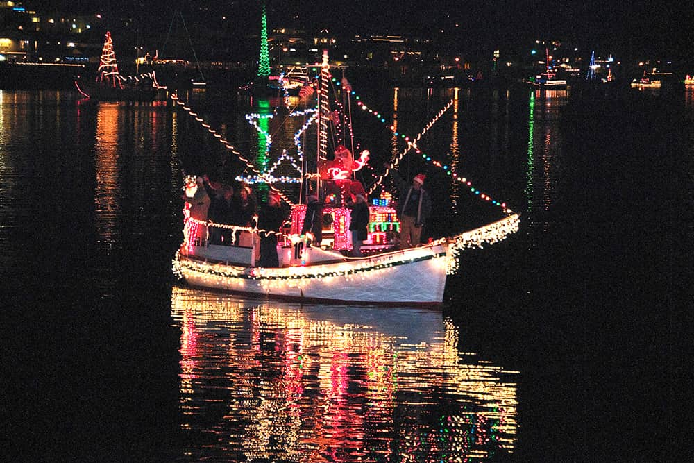 boat decorated with christmas lights in morro bay
