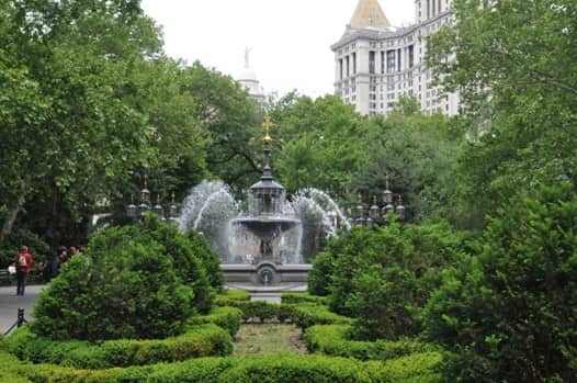 Fountain surrounded by bushes in City Hall Park in New York City