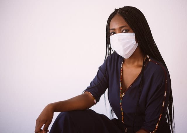 black woman with long hair wearing fce mask posed in front of white wall