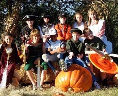 children sitting on pumpkins