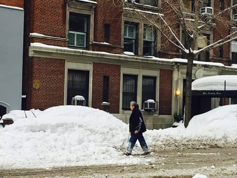 Older woman walking by cars that are covered by snow in NYC