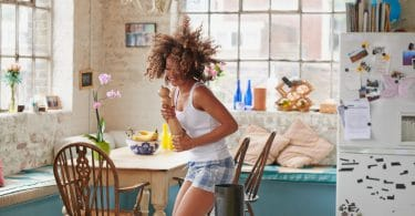 Happy woman dancing in well-lit kitchen
