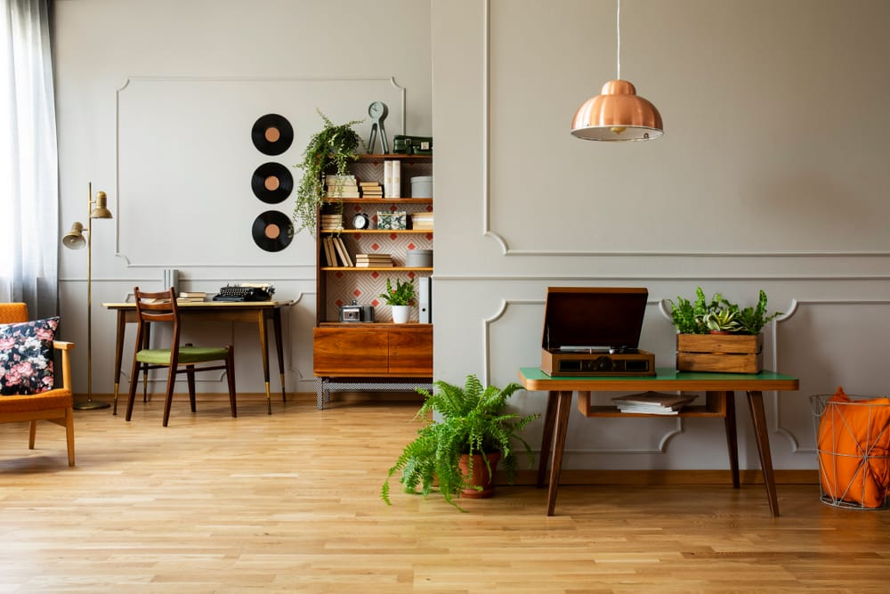 Record player and plant on wooden table in grey apartment interior with lamp and vinyl