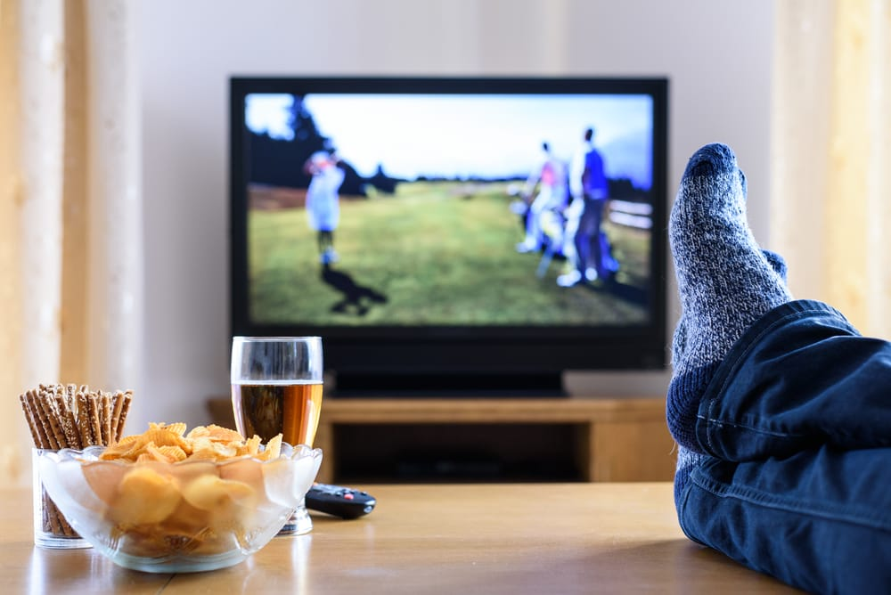 TV watching (golf game) in living room with feet on table