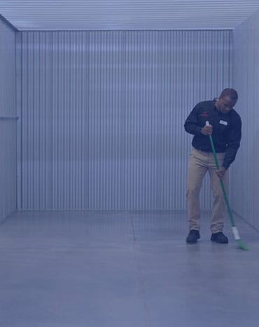 CubeSmart employee sweeping clean a unit