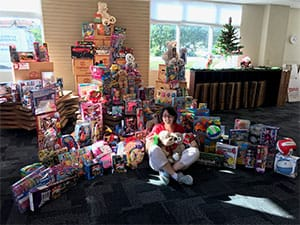 Woman sitting in front a large amount of presents